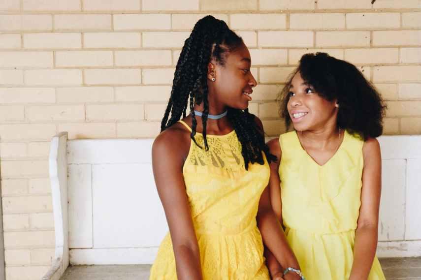 two girls wearing yellow sleeveless dresses