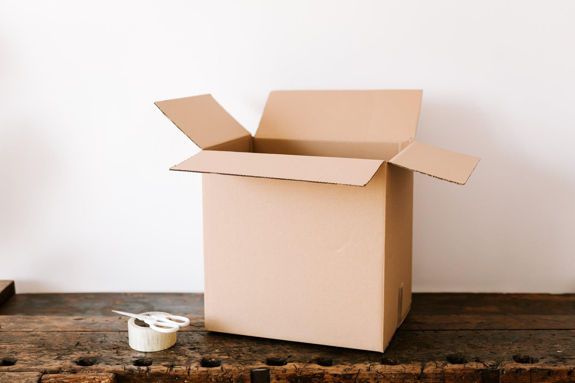 cardboard box on dark wooden table near tape and scissors